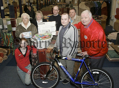 PIctured with Big'O' are JT Carpets annual Christmas Raffle winners. 06W1N3
