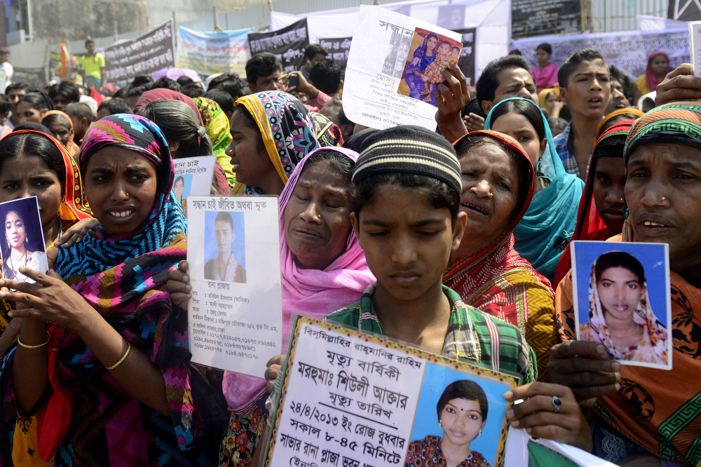 . Bangladeshi relatives of missing garment workers take part in a protest marking the first anniversary of the Rana Plaza building collapse in Dhaka on April 24, 2014. The Rana Plaza building collapsed on April 24, 2013, killing 1138 workers in the world\'s worst garment factory disaster. Western fashion brands faced pressure to increase help for victims as mass protests marked the anniversary. Thousands of people, some wearing funeral shrouds, staged demonstrations at the site of the now-infamous Rana Plaza factory complex.  (MUNIR UZ ZAMAN/AFP/Getty Images)