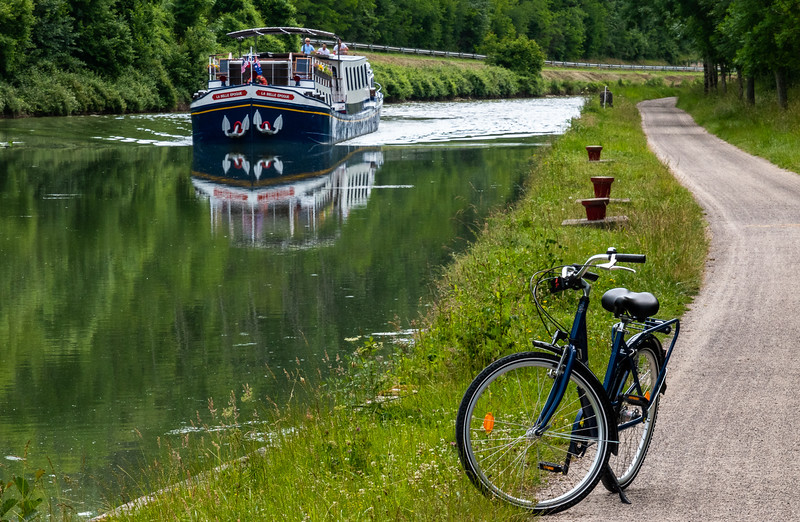 smalle barge in the background with bike on river path