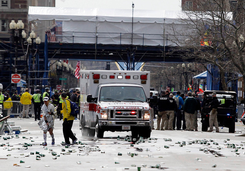 . A runner is escorted from the scene after explosions went off at the 117th Boston Marathon in Boston, Massachusetts April 15, 2013. Two explosions hit the Boston Marathon as runners crossed the finish line on Monday, killing at least two people and injuring 23 on a day when tens of thousands of people pack the streets to watch one of the world\'s best known marathons. REUTERS/Jessica Rinaldi