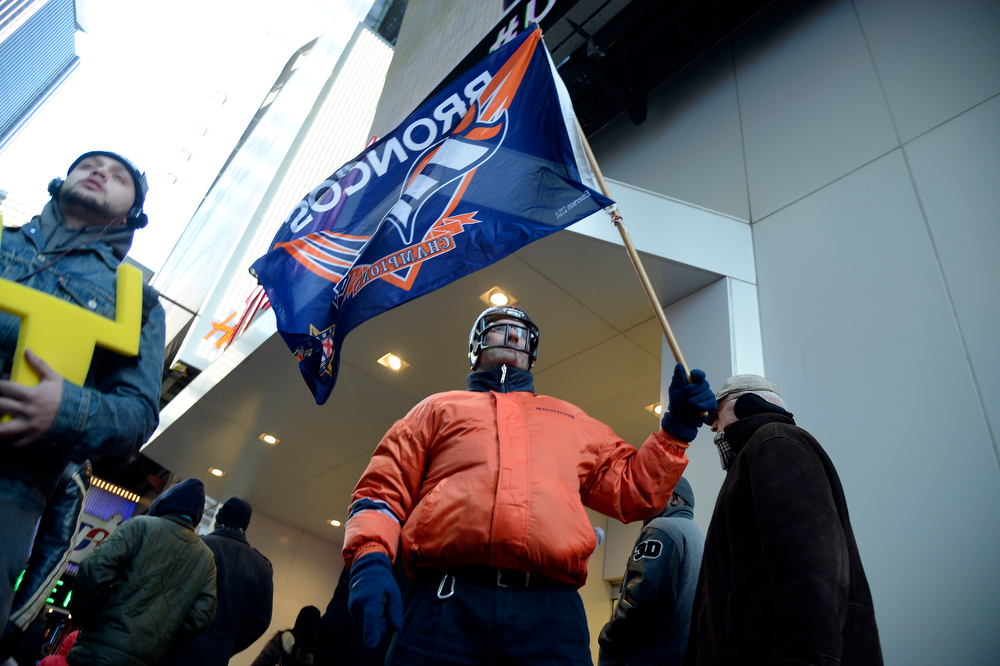 Description of . Denver Broncos fan Brian Carey walks the streets with his Denver Broncos flag as Super Bowl XLVlll fans hit Times Square to enjoy the Super Bowl Boulevard. The NFL transformed a portion of Broadway into the sports and entertainment hub of Super Bowl Week, January 29, 2014. (Photo by John Leyba/The Denver Post)
