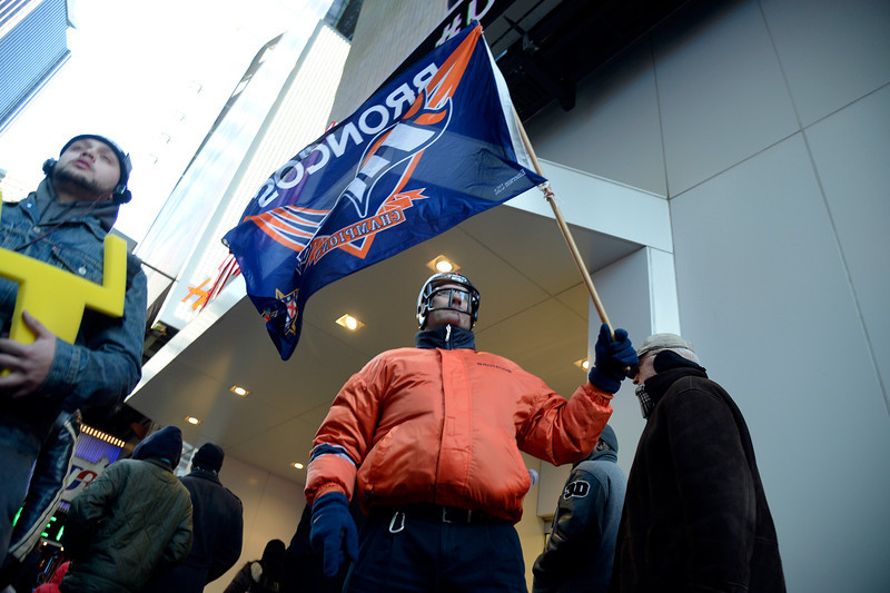 . Denver Broncos fan Brian Carey walks the streets with his Denver Broncos flag as Super Bowl XLVlll fans hit Times Square to enjoy the Super Bowl Boulevard. The NFL transformed a portion of Broadway into the sports and entertainment hub of Super Bowl Week, January 29, 2014. (Photo by John Leyba/The Denver Post)