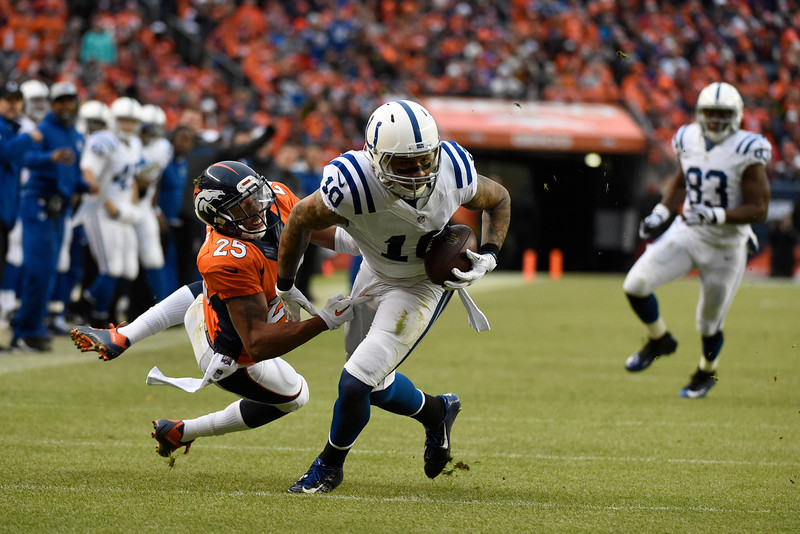 . Donte Moncrief (10) of the Indianapolis Colts makes a catch and is brought down by Chris Harris (25) of the Denver Broncos in the second quarter. The Denver Broncos played the Indianapolis Colts in an AFC divisional playoff game at Sports Authority Field at Mile High in Denver on January 11, 2015. (Photo by John Leyba/The Denver Post)