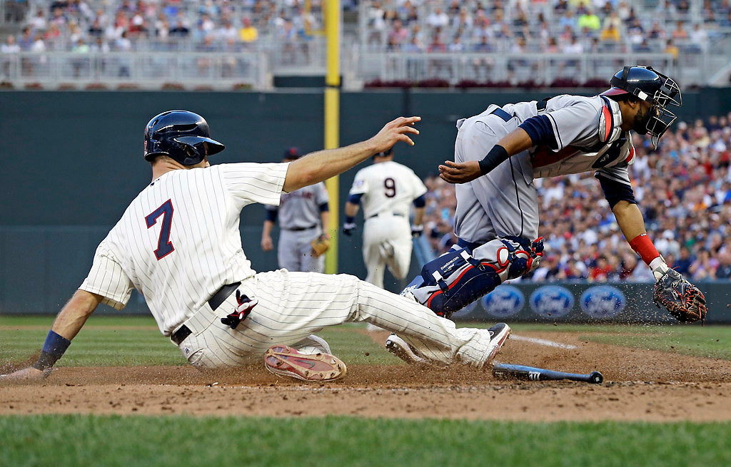 . Minnesota Twins\' Joe Mauer, left, scores on an error as Cleveland Indians catcher Carlos Santana races for the wide throw from Indians third baseman Lonnie Chisenhall in the sixth inning. (AP Photo/Jim Mone)