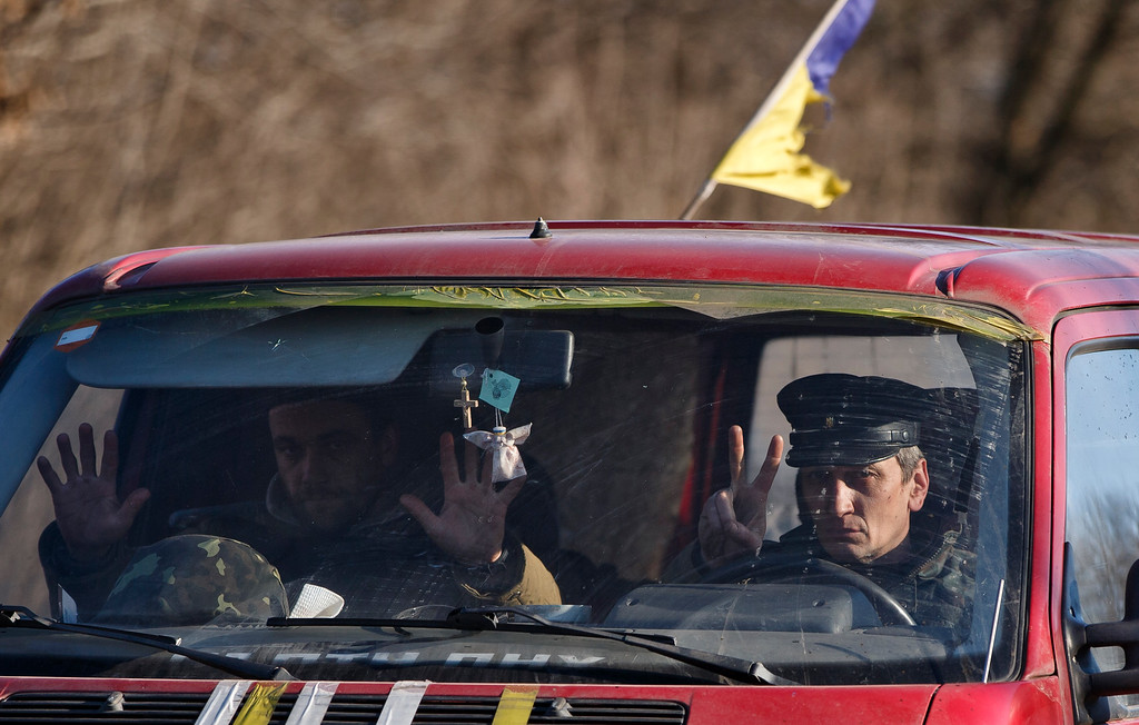 . Ukrainian servicemen gesture from a vehicle outside Artemivsk, Ukraine, while pulling out of Debaltseve, Wednesday, Feb. 18, 2015. After weeks of relentless fighting, the embattled Ukrainian rail hub of Debaltseve fell Wednesday to Russia-backed separatists, who hoisted a flag in triumph over the town. The Ukrainian president confirmed that he had ordered troops to pull out and the rebels reported taking hundreds of soldiers captive. (AP Photo/Vadim Ghirda)