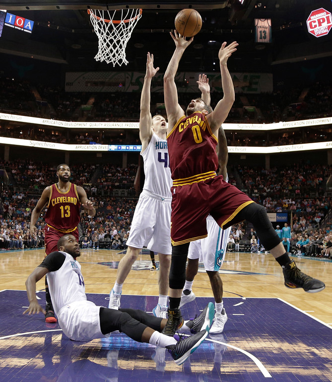 . Cleveland Cavaliers\' Kevin Love (0) shoots over Charlotte Hornets\' Cody Zeller (40) and Michael Kidd-Gilchrist (14) during the first half of an NBA basketball game in Charlotte, N.C., Friday, March 24, 2017. (AP Photo/Chuck Burton)