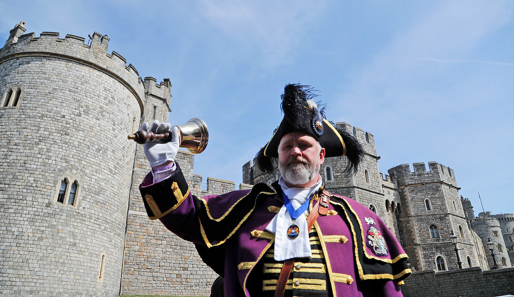 . A cryer rings his bell in front of Windsor Castle in Windsor, Friday, May 18, 2018. Preparations are being made in the town ahead of the wedding of Britain\'s Prince Harry and Meghan Markle that will take place in Windsor on Saturday May 19.(AP Photo/Frank Augstein)