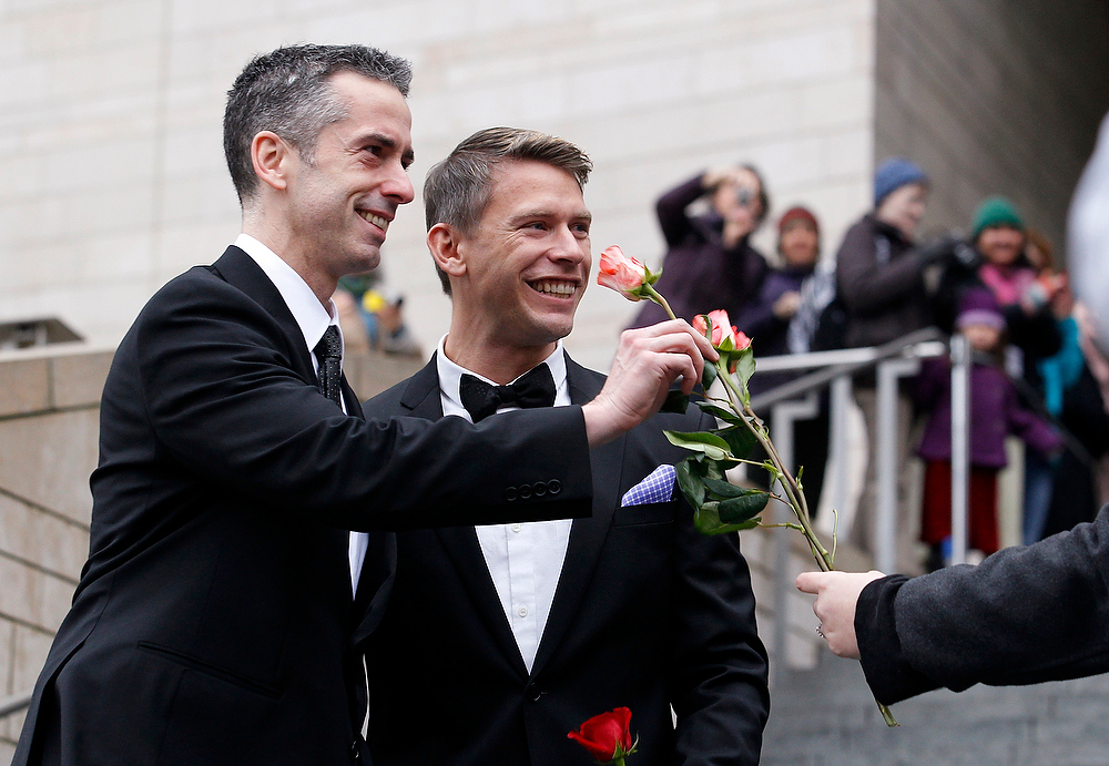 . Dan Savage, left, and his husband Terry Miller are handed flowers after their wedding at Seattle City Hall, Sunday, Dec. 9, 2012, in Seattle. (AP Photo/Elaine Thompson)