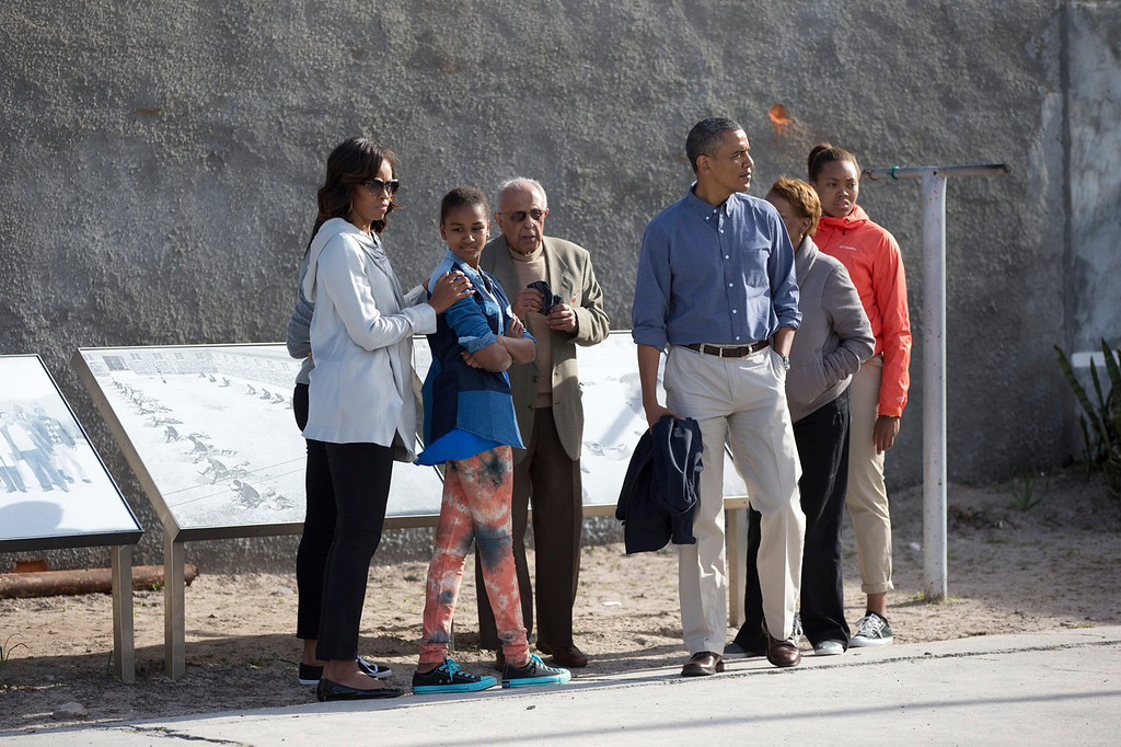 . From left, first lady Michelle Obama, Sasha Obama, Ahmed Kathrada, former prisoner with Nelson Mandela guiding the tour, U.S. President Back Obama, Marian Robinson and Leslie Robinson, look out over the courtyard of the prison on Robben Island, South Africa, Sunday, June 30, 2013. Former South African president Nelson Mandela spent 18 years of his 27-year prison term on the island locked up by the former apartheid government.  (AP Photo/Carolyn Kaster)