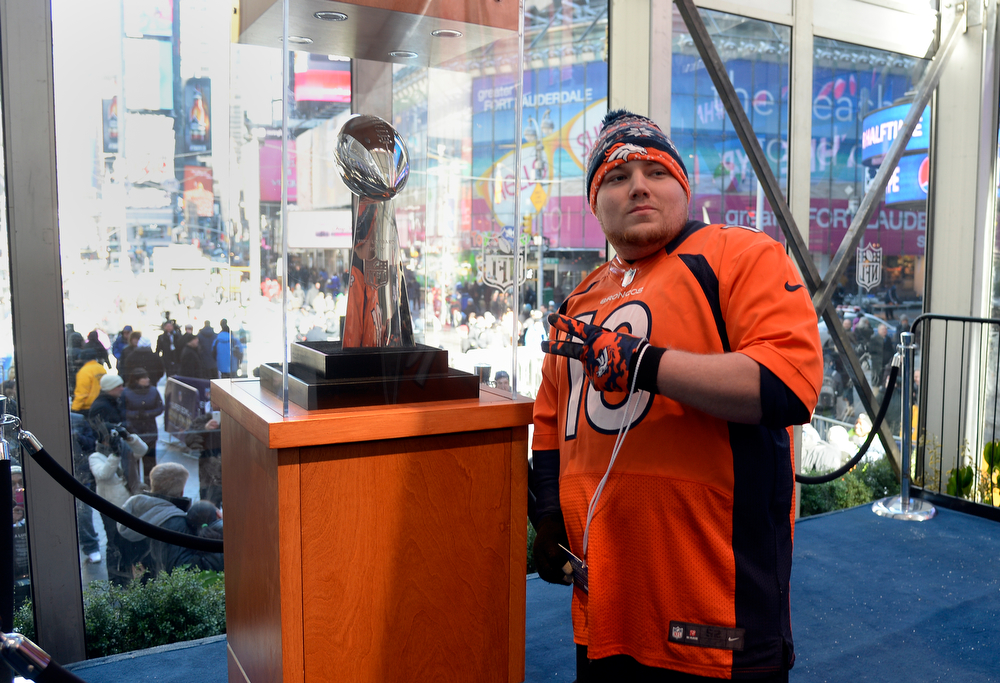 Description of . Denver Broncos fan Corey Marte of Suffern, NY has a photo taken with the Vince Lombardi Trophy as Super Bowl XLVlll fans hit Times Square to enjoy the Super Bowl Boulevard. The NFL transformed a portion of Broadway into the sports and entertainment hub of Super Bowl Week, January 29, 2014. (Photo by John Leyba/The Denver Post)