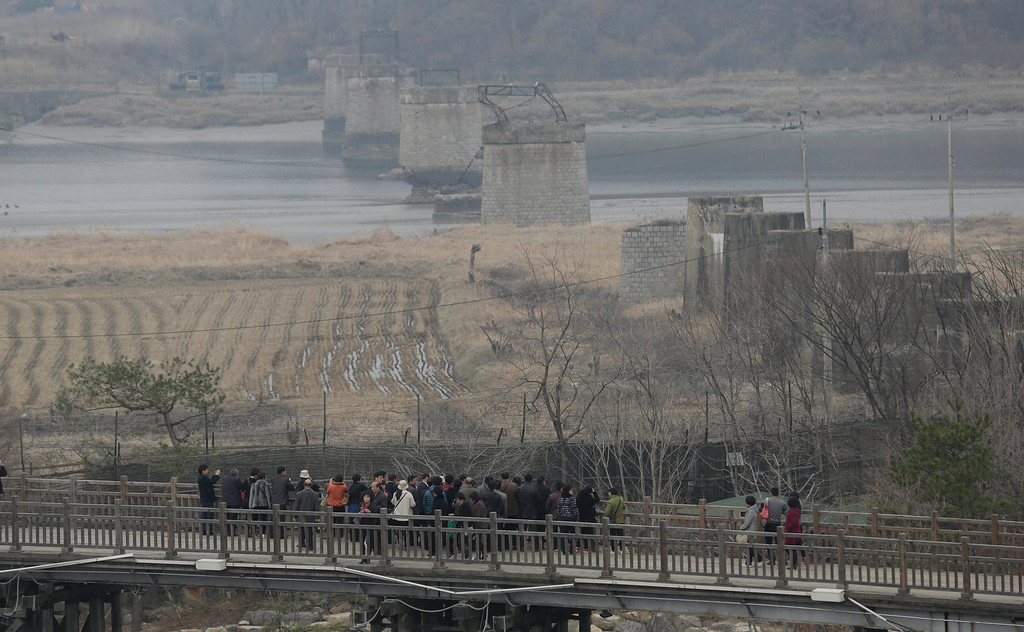 """. Tourists look over the north side of the Bridge of Freedom which was destroyed during the Korean War, at the Imjingak Pavilion near the border village of the Panmunjom, which has separated the two Koreas since the Korean War, in Paju, north of Seoul, South Korea, Friday, April 5, 2013. After a series of escalating threats, North Korea moved a missile with \""""considerable range\"""" to its east coast, South Korean Defense Minister Kim Kwan-jin said Thursday. But he emphasized that the missile was not capable of reaching the United States and that there are no signs that the North is preparing for a full-scale conflict. (AP Photo/Lee Jin-man)"""