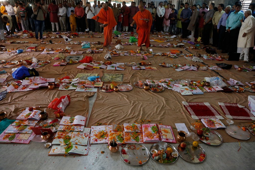 . Hindu saints sprinkle red vermilion powder on account books lying on the ground during Chopada Pujan, or a mass prayer ceremony dedicated to the worship of the account book, on the occasion of Diwali, the Hindu festival of lights, in Ahmadabad, India, Thursday, Oct. 19, 2017. During Chopada Pujan ledgers and new account books are opened by the mercantile community following a special prayer and worship before the idols of Lord Ganesha and Hindu Goddess of wealth Lakshmi to earn their blessings. (AP Photo/Ajit Solanki)