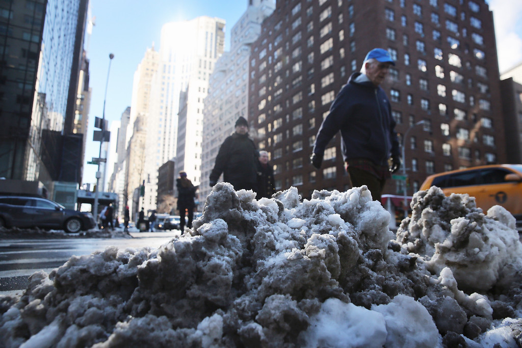 . NEW YORK, NY - JANUARY 23:  People walk past a bank of dirty snow in Midtown Manhattan on January 23, 2014 in New York City. Although temperatures climed out of the teens Thursday, ice on streets and sidewalks made it difficult moving around the city.  (Photo by John Moore/Getty Images)