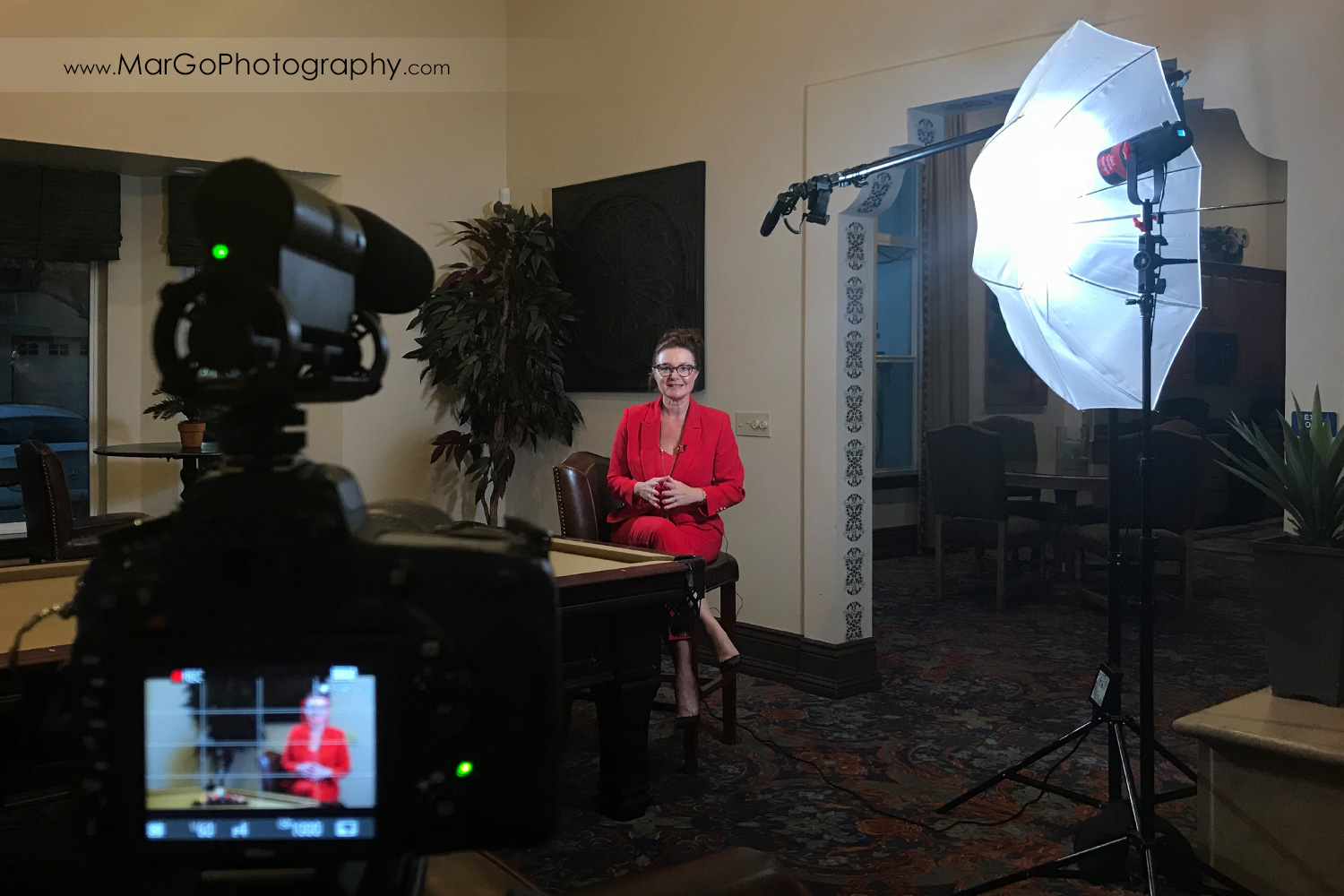 behind the scenes of indoor filming woman speaker in red suit witting on the chair behind the pool table