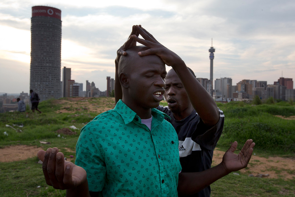 . People offer prayers on a hill overlooking the city of Johannesburg, South Africa, Saturday Dec. 7, 2013.  South Africa is readying itself for the arrival of a flood of world leaders for the memorial service and funeral for Nelson Mandela as thousands of mourners continued to flock to sites around the country Saturday to pay homage to the freedom struggle icon. (AP Photo/Peter Dejong)
