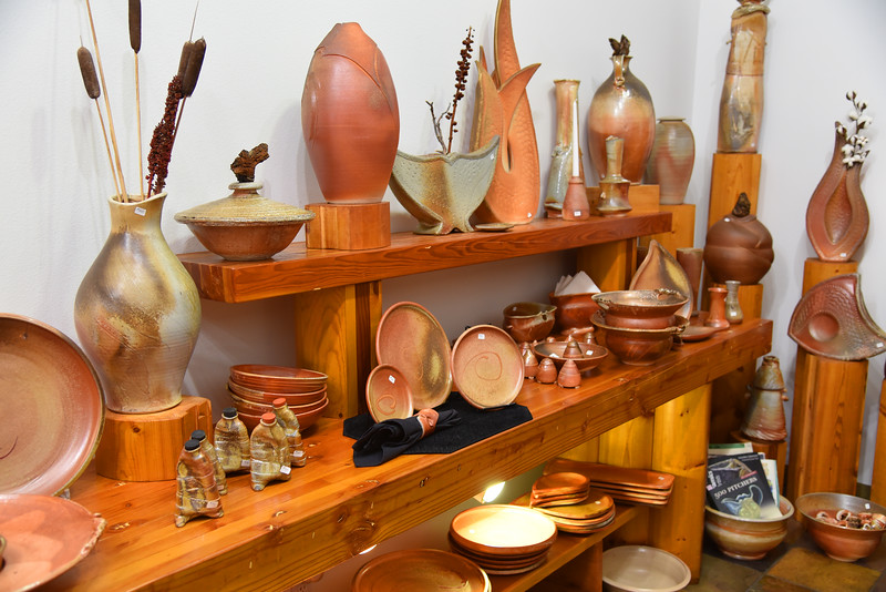 display of pottery on wooden shelves