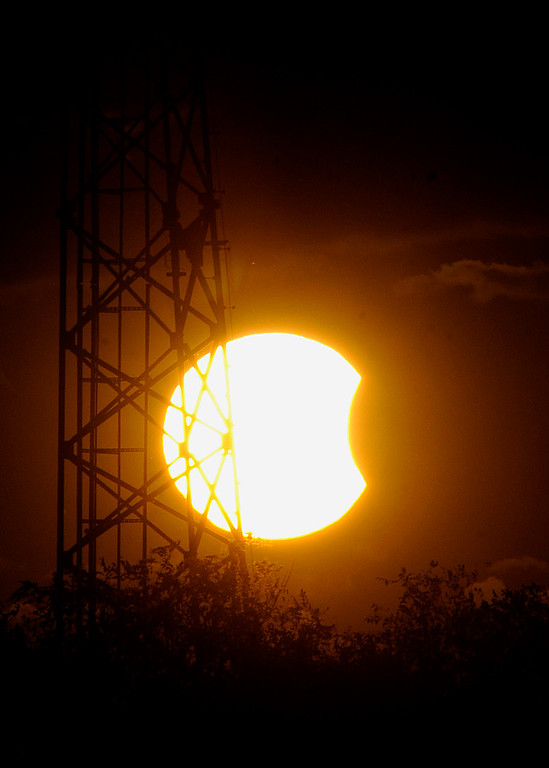 . A partial solar eclipse is visable through a cell tower just before sunset Thursday, Oct. 23, 2014, in Martinsburg, W.Va. (AP Photo/The Journal, Ron Agnir)