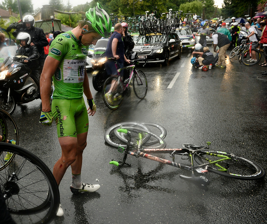. Peter Sagan of Slovakia, wearing the best sprinter\'s green jersey, waits for assistance after he crashed in the last three kilometers of the nineteenth stage of the Tour de France cycling race over 208.5 kilometers (129.6 miles) with start in Maubourguet and finish in Bergerac, France, Friday, July 25, 2014. (AP Photo/Lionel Bonaventure, Pool)