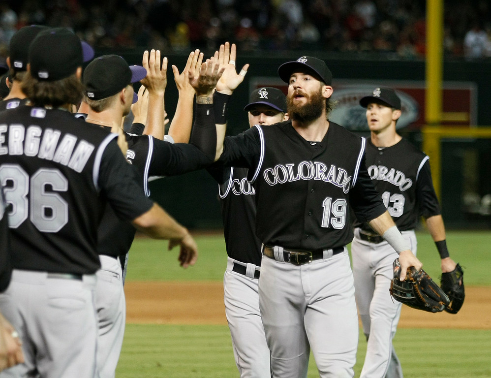 . Colorado Rockies right fielder Charlie Blackmon (19) celebrates with teammates after defeating the Arizona Diamondbacks 2-0 during a baseball game, Saturday, Aug. 30, 2014, in Phoenix. (AP Photo/Rick Scuteri)