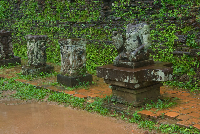 Small pillars and headless statue in My Son Sanctuary, Vietnam