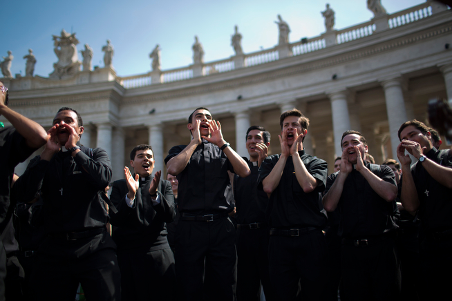 . Priests sing and dance in St. Peter\'s Square at the Vatican, Saturday, April 26, 2014. Pilgrims and faithful are gathering in Rome to attend Sunday\'s ceremony at the Vatican where Pope Francis will elevate in a solemn ceremony John XXIII and John Paul II to sainthood. (AP Photo/Emilio Morenatti)