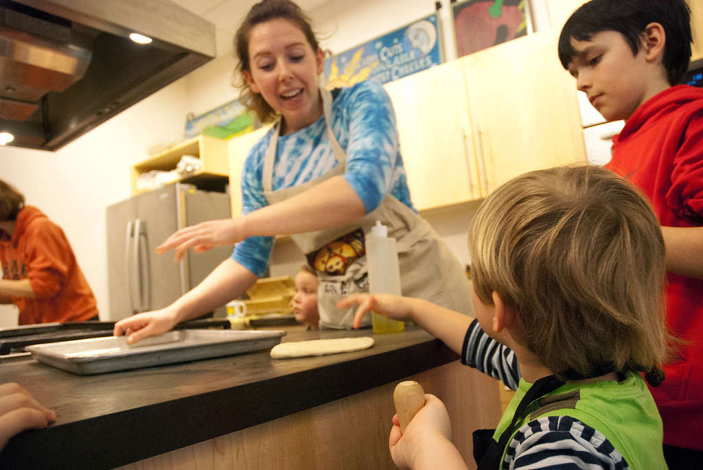 . Kayla Rice/Reformer Lauren Manning of Brattleboro helps children flatten out their pizza dough during a Winter Carnival cooking class at the Brattleboro Food Co-Op on Friday afternoon.