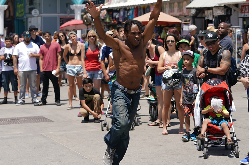 A street performed prepares to do a flip in Venice Beach