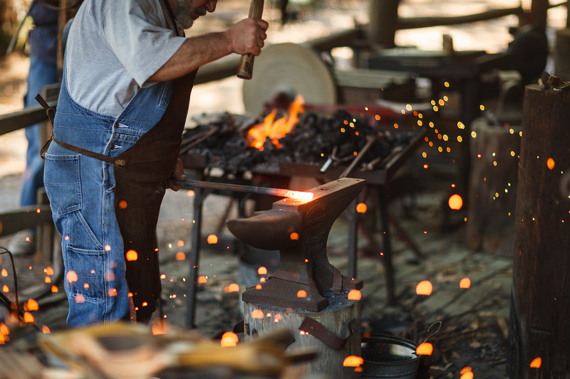 A man forging a piece of metal.