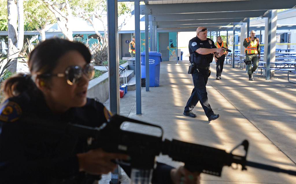. The Hermosa Beach and Manhattan Beach Police Depts. conducted an active shooter drill on the campus of Hermosa Valley School Monday, November 25, 2013, Hermosa Beach, CA.   Officers responded to staged calls of a gun man on the campus, had to find and neutralize the suspect. Students also participated in the drill to give it more realism. Officers engage the suspect as he fires blanks from a doorway. Photo by Steve McCrank/DailyBreeze
