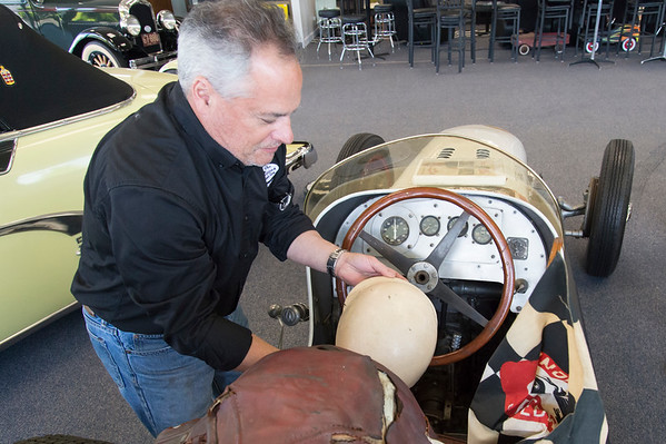 05/15/19 Wesley Bunnell | Staff Michael Donnelly, President of The Paddock Classic Car Restorations, examines a helmet worn by race car drivers during the 1940's and 1950's inside of a custom built race car named the Marchese Special. The race car which was built in the early 1940's competed in the Indianapolis 500 until 1951.