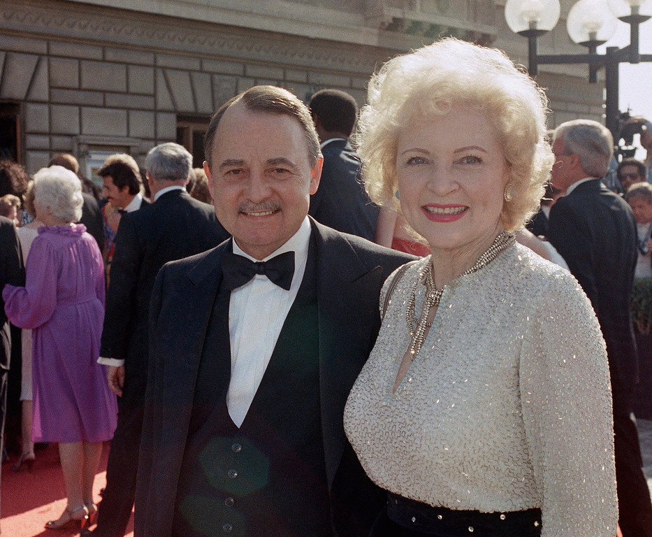 . FILE- This Sept. 22, 1985, file photo shows John Hillerman, left, and Betty White, right, arriving at Emmy Awards in Pasadena, Calif. A spokeswoman for the family of Hillerman says the co-star of TV�s �Magnum, P.I.� died Nov. 9. Hillerman was 84. Spokeswoman Lori De Waal said Hillerman died Thursday at his home in Houston. She said the cause of death has yet to be determined. (AP Photo/LIU, File)