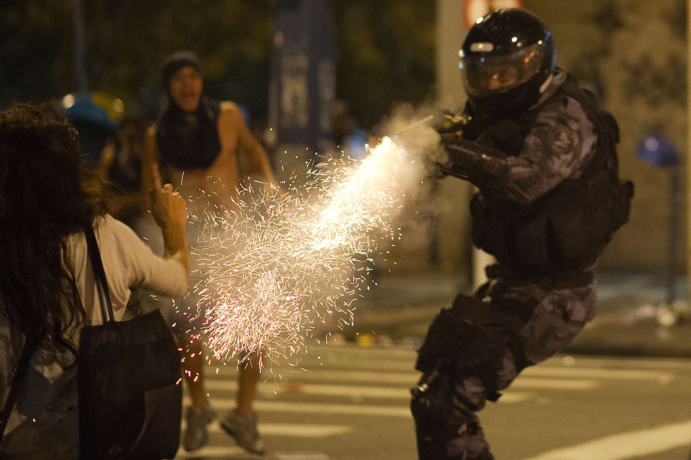 . A military police from the special unit Chope shoots with a tear gas gun late on June 19, 2013 to disperse protestors during clashes in the center of Niteroi, 10 kms from Rio de Janeiro. Protesters battled police late on June 19, even after Brazil\'s two biggest cities rolled back the transit fare hikes that triggered two weeks of nationwide protests.  The fare rollback in Sao Paulo and Rio de Janeiro marked a major victory for the protests, which are the biggest Brazil has seen in two decades.   CHRISTOPHE SIMON/AFP/Getty Images