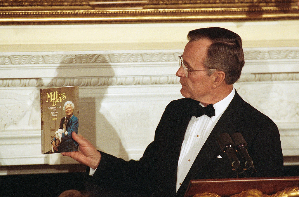 """. U.S. President George H. Bush holds up the German-language version of \""""Millie\'s Book\"""" written by Barbara Bush and the Bush\'s dog Millie. Bush presented the book to German President Richard Von Weizsaecker during a state dinner in his honor at the White House in Washington, Wednesday, April 29, 1992. (AP Photo/Doug Mills)"""