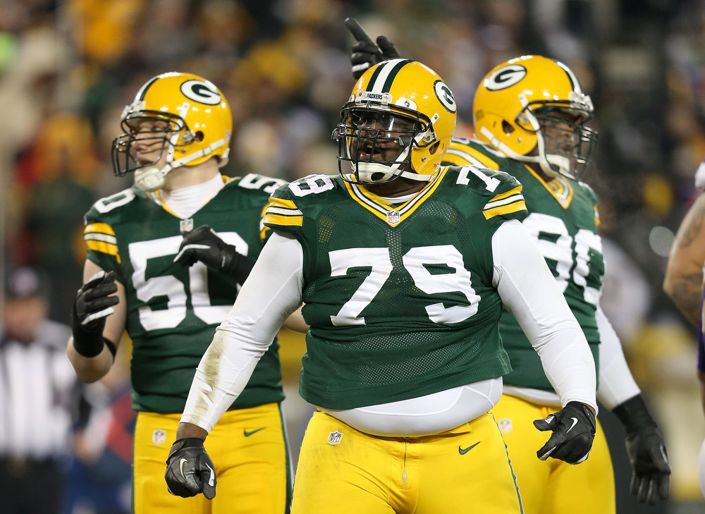Description of . (C) Defensive end Ryan Pickett #79 of the Green Bay Packers reacts in front of teammates inside linebacker A.J. Hawk #50 and nose tackle B.J. Raji #90 in the second quarter against the Minnesota Vikings during the NFC Wild Card Playoff game at Lambeau Field on January 5, 2013 in Green Bay, Wisconsin.  (Photo by Andy Lyons/Getty Images)