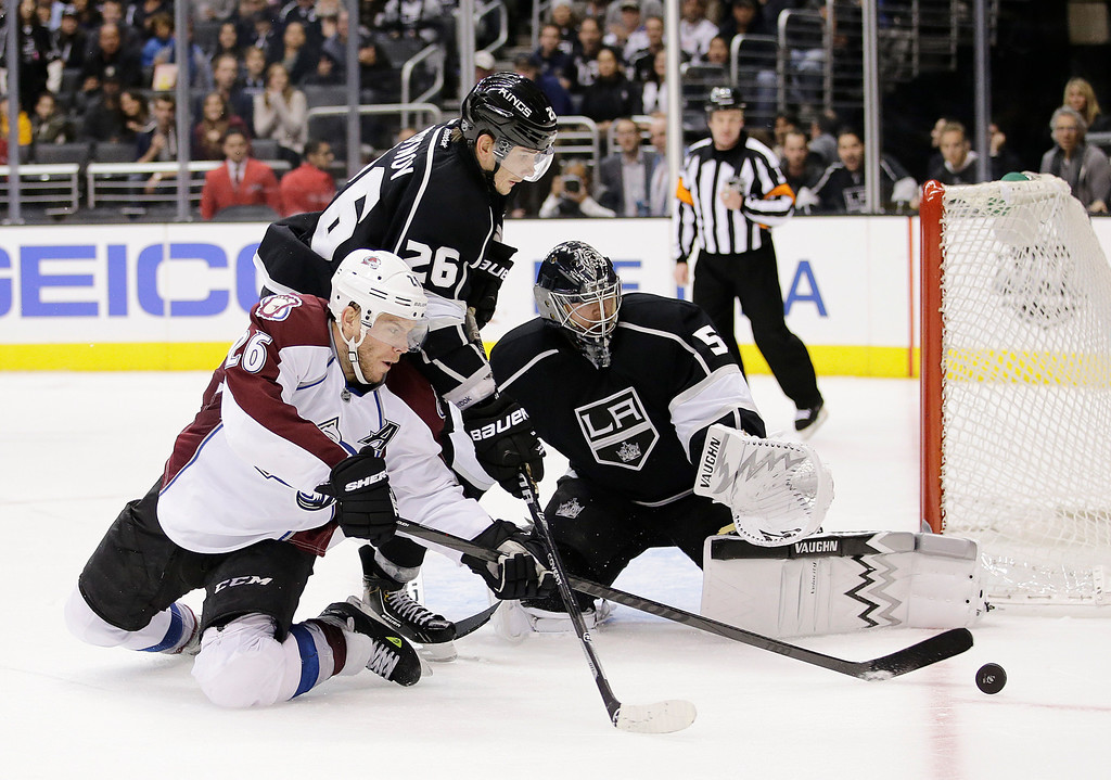 . Los Angeles Kings\' Slava Voynov, top, of Russia, and Colorado Avalanche\'s Paul Stastny go after the puck as Los Angeles Kings goalie Ben Scrivens, right, looks on during the third period of an NHL hockey game on Saturday, Nov. 23, 2013, in Los Angeles. The Avalanche won 1-0 in overtime. (AP Photo/Jae C. Hong)