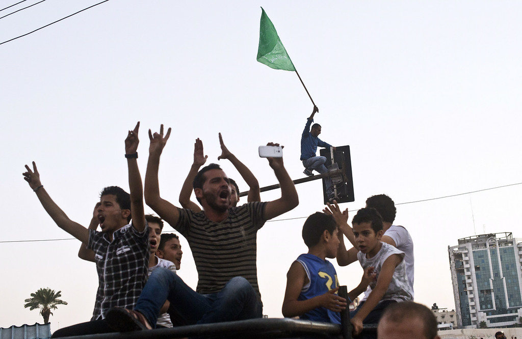 . Palestinian men flash the sign of victory on the top of a car in front of a man planting a Hamas flag atop a street light as people gather at an intersection in Gaza City to celebrate the ceasefire between Israel and Hamas on August 26, 2014. Egypt said that a Gaza ceasefire that went into force at 1600 GMT provides for an immediate opening of Israeli border crossings to aid and reconstruction supplies. ROBERTO SCHMIDT/AFP/Getty Images