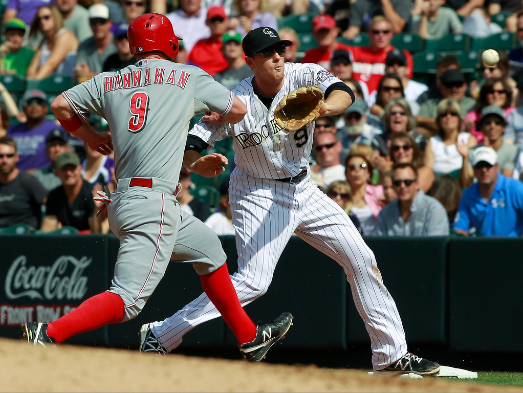 . Colorado Rockies second baseman DJ LeMahieu, right, fields throw to put out Cincinnati Reds\' Jack Hannahan, left, on the back end of a double play when Hannahan was caught leaning off first base in the fourth inning of a baseball game in Denver, Sunday, Sept. 1, 2013. (AP Photo/David Zalubowski)
