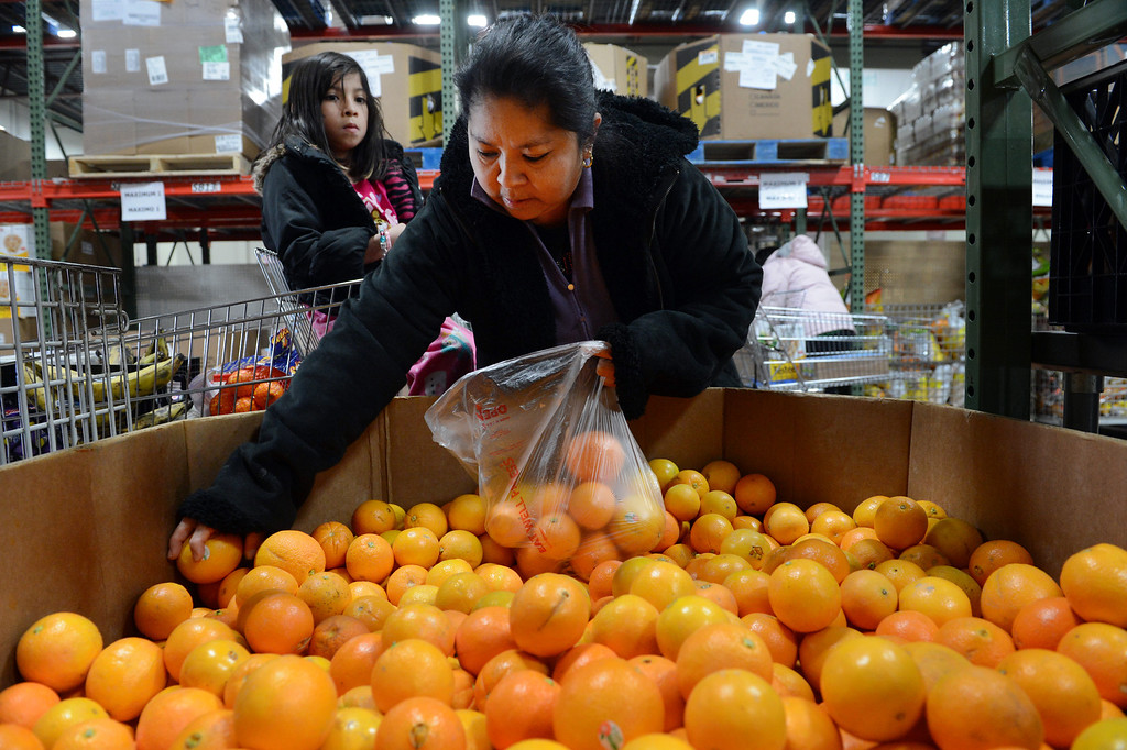 . Elizabeth Ramirez and her daughter Jacqueline, 7, selects oranges in the Feeding Families shopping area at the Community Food Share in Longmont, CO, Thursday December 27, 2012.  Craig F. Walker, The Denver Post