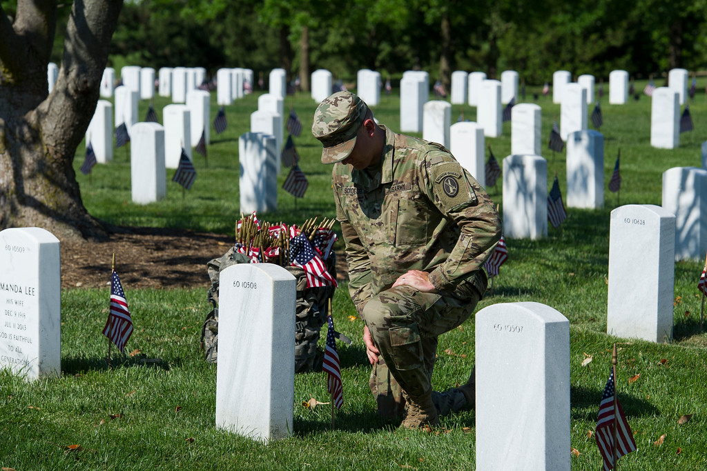 . A member of the Army 3d U.S. Infantry Regiment, The Old Guard, pauses to honor a fallen soldier while places flags a the gravesite of the nation\'s fallen military heroes during its annual Flags In ceremony at Arlington National Cemetery, Thursday, May 24, 2018, in Arlington, Va. (AP Photo/Cliff Owen)