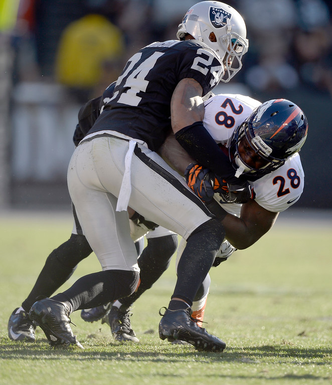 . Denver Broncos running back Montee Ball (28) is brought down by Oakland Raiders free safety Charles Woodson (24) during the first quarter at O.co Coliseum. (Photo by John Leyba/The Denver Post)