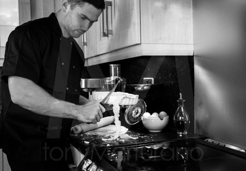 Good looking male chef cutting off excess pastry from dish