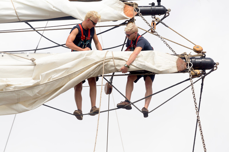 Two crewmen reefing a mainsail