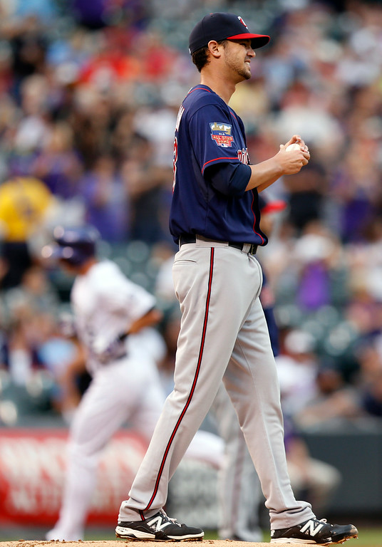 . Minnesota Twins starting pitcher Kris Johnson reacts to giving up a two run home run to Colorado Rockies\' Drew Stubbs against the Colorado Rockies during the first inning of a baseball game on Friday, July 11, 2014, in Denver. (AP Photo/Jack Dempsey)