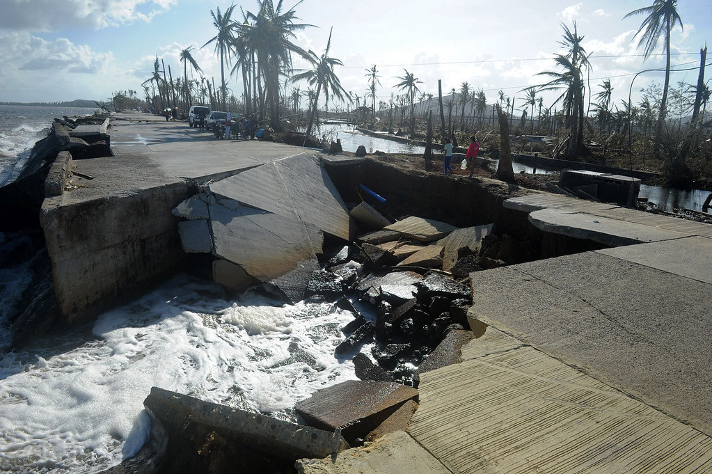 . Residents cross a collapsed highway caused by the storm surge in Palo, eastern island of Leyte on November 10, 2013, three days after devastating Super Typhoon Haiyan hit the area on November 8. The death toll from a super typhoon that decimated entire towns in the Philippines could soar well over 10,000, authorities warned on November 10, making it the country\'s worst recorded natural disaster.  NOEL CELIS/AFP/Getty Images