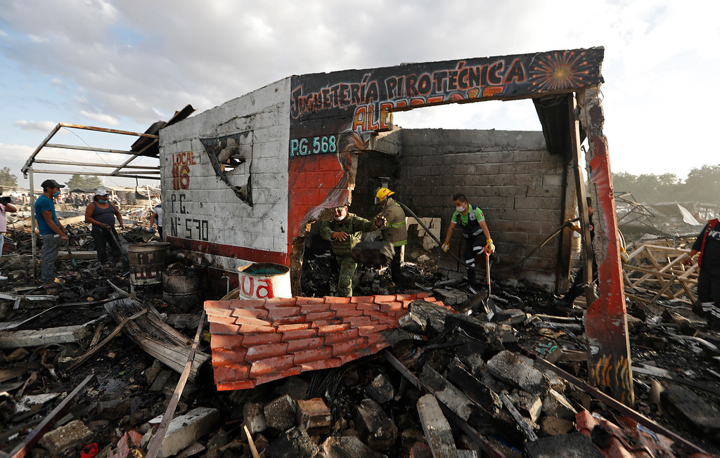 . Firefighters and rescue workers remove debris from the scorched ground of Mexico\'s best-known fireworks market after an explosion explosion ripped through it, in Tultepec, on the outskirts of Mexico City, Mexico, Tuesday, Dec. 20, 2016. National Civil Protection Coordinator Luis Felipe Puente told Milenio TV that dozens were hurt but he had no immediate report of any fatalities at the open-air San Pablito Market in Tultepec, in the State of Mexico. (AP Photo/Eduardo Verdugo)