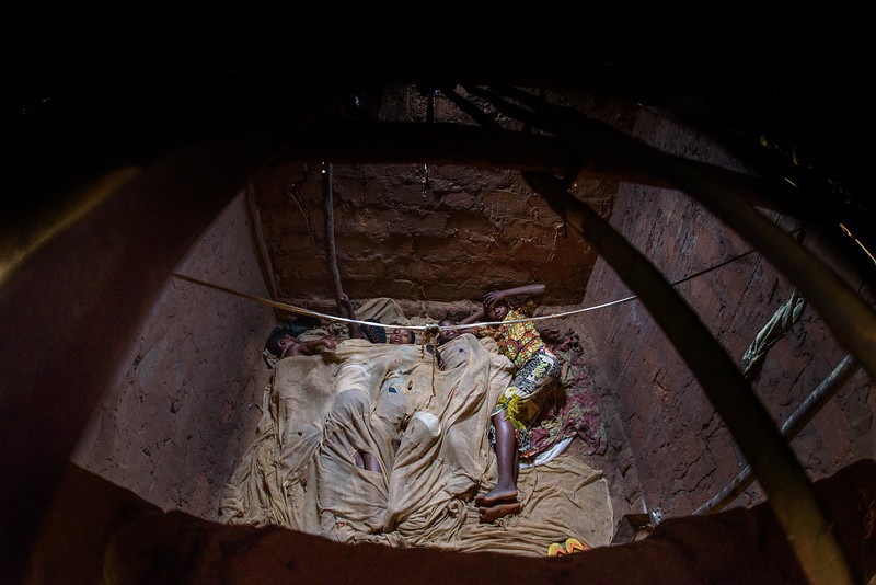 """Each night when she goes to bed, Marie Ngalula, 14 yr-old girl, and her siblings all sleep together in one room, huddled together for warmth and cover by an old and torn mosquito net. Tubuluku, Kananga, DRC.  Marie lives with her father, Alexandre Tshimanga, her mother, Ntumba Kalombo Antoinette and her brothers and sisters: 1-Kena Tshimanga, 12 2-Kankonde Moise, 10 3-Munamba Angel, 8 4-Musungayi Andre, 6 5-Mubuyi Tshimanga, 4  Marie lives in a small village outside of Kananga, Democratic Republic of Congo, DRC, called Tubuluku, which means antelopes (plural). Her house is a two-room hut with a thatched roof.  Handful of wooden chairs are the only furniture. She lives here with an extended family of 13.  Home Life Marie is a bright girl but there is a sadness in her eyes. Marie's mother is in the nearby health clinic with a staph infection that has caused a huge abscess on her right side. It has become very serious. As a result, Marie has assumed many of the household duties.  She's forced, at 14, to assume the duties of an adult. Besides cooking for her brothers and sisters, she sweeps up the husks from palm nuts she crushes. She saves the husks to use as kindling for the fire. Marie and her siblings all sleep together in one room, huddled together for warmth and cover by an old and torn mosquito net.  School Marie's father laments his inability to send her back to school. """"Marie is intelligent,"""" he says. """"She could help me very much someday.  I'd like to send her back to school but I can't afford it. I'd like if she could further her studies even as far as university so that she can help me take care of her brothers and sisters someday.""""  Marie and her friends often play on the grass in front of the school they can't afford to go to.  Hunger Marie's family is desperately hungry in the days we visit them. Because her mother is sick and his father spends his days tending to her in the clinic, there is no money for food. Because there isn't any cassava flour and corn"""