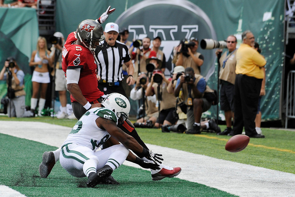 . New York Jets linebacker Antwan Barnes (95) and Tampa Bay Buccaneers quarterback Josh Freeman (5) chase after the ball in the first half of an NFL football game, Sunday, Sept. 8, 2013, in East Rutherford, N.J. The ball went out of the end zone for a safety. (AP Photo/Bill Kostroun)