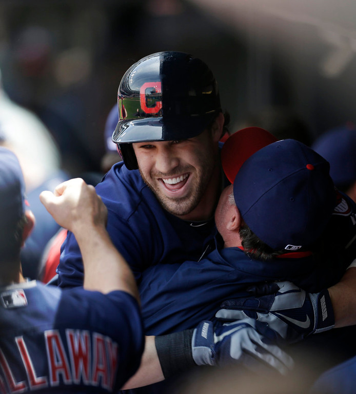 . Cleveland Indians\' Jason Kipnis is picked up by Jason Giambi in the dugout after Kipnis hit a solo home run off Minnesota Twins starting pitcher Kevin Correia in the first inning. (AP Photo/Tony Dejak)