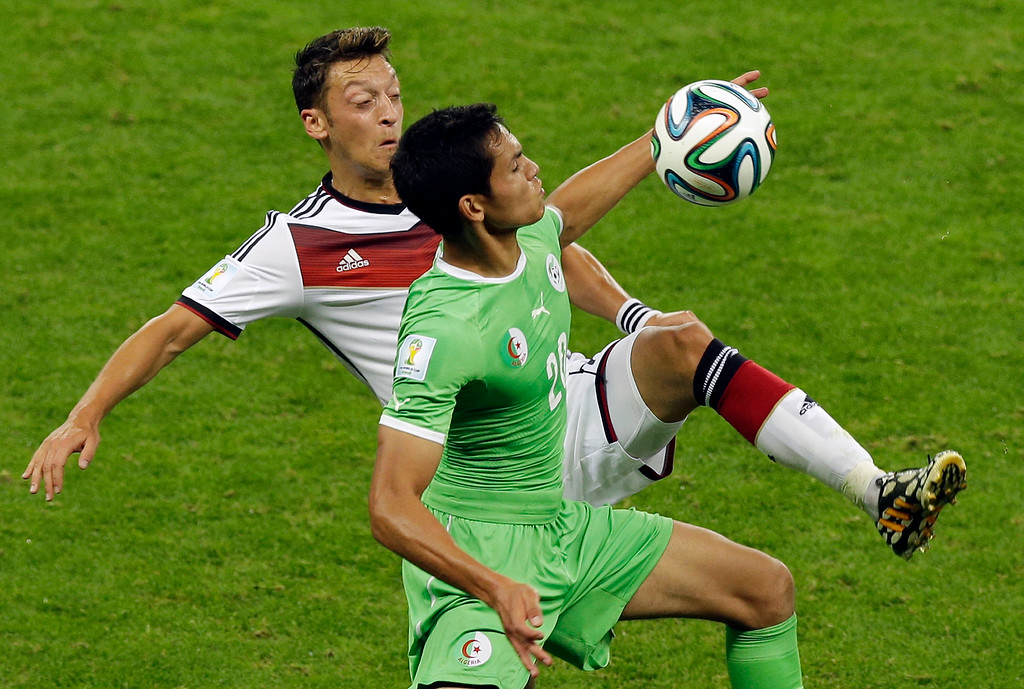 . Germany\'s Mesut Ozil, left, and Algeria\'s Aissa Mandi challenge for the ball during the World Cup round of 16 soccer match between Germany and Algeria at the Estadio Beira-Rio in Porto Alegre, Brazil, Monday, June 30, 2014. (AP Photo/Thanassis Stavrakis)