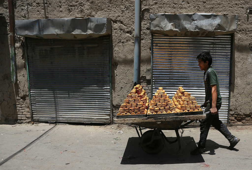 . An Afghan young boy carries traditional sweets with a hand cart at a market to be displayed for sale for the upcoming Eid al-Fitr holiday to mark the end of the holy fasting month of Ramadan, in the old part of Kabul, Afghanistan, Wednesday, June 13, 2018. (AP Photo/Rahmat Gul)